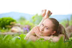 Portrait of young beautiful woman lying in grass Royalty Free Stock Photography