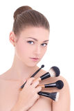 Portrait of young beautiful woman with make up brushes isolated Stock Image