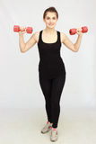 Portrait of young beautiful woman making physical exercises with dumbbells Royalty Free Stock Image