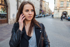 Portrait of young beautiful woman with mobile phone. Urban style Stock Photography