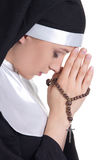 Portrait of young beautiful woman nun praying with rosary isolat stock photos