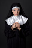 Portrait of young beautiful woman nun praying with rosary over g Stock Images