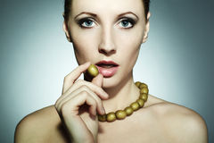Portrait of the young beautiful woman with olives Stock Photography