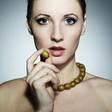 Portrait of the young beautiful woman with olives Stock Photos