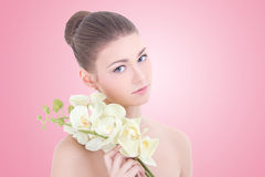 Portrait of young beautiful woman with orchid flower over pink Stock Photography