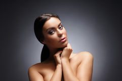 Portrait of a young and beautiful woman over grey Stock Images