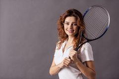 Female studio shooting. Portrait of a young beautiful woman while playing tennis on a gray background holding a tennis racket on her shoulder and a smile to the royalty free stock photography