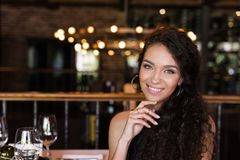Portrait of young beautiful woman. Sitting in restaurant, smiling and looking at camera Stock Images
