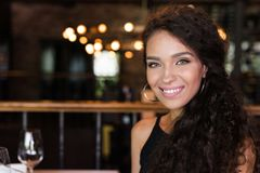 Portrait of young beautiful woman. Sitting in restaurant, smiling and looking at camera Stock Photos