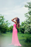 Portrait of young beautiful woman posing among spring blooming trees. Royalty Free Stock Image