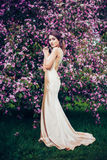 Portrait of young beautiful woman posing among spring blossom trees. Royalty Free Stock Images