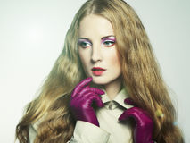 Portrait of young beautiful woman in purple gloves Stock Photo