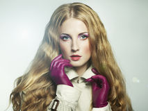 Portrait of young beautiful woman in purple gloves Stock Image