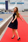 Portrait of young beautiful woman on the red carpet of the air show.  Royalty Free Stock Photos