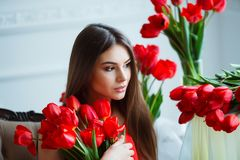 Portrait of young beautiful woman in red dress with tulips in luxury interior. Royalty Free Stock Photos