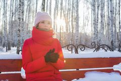 Young beautiful woman in red warm jacket sits on bench in pictorial park with birches and warms hands in winter frosty sunny day royalty free stock photography
