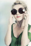Portrait of young beautiful woman in the round sunglasses. On light background royalty free stock photography