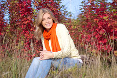 Portrait of young beautiful woman sitting in autumn park Stock Photos