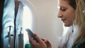 Portrait of young beautiful woman sitting near the window in plane and using the smartphone. Female and man traveling. stock video footage