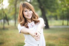 Portrait of young beautiful woman smiling in the park with lollipop Royalty Free Stock Photography