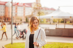 Portrait of young beautiful woman smiling to camera in city on bulding background in sunny spring day. Portrait of cute girl smiling to camera in city on bulding Stock Photography