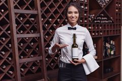 Portrait of young beautiful woman. Sommelier standing with bottle of wine and glass in cellar Stock Photos