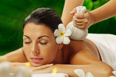 On massage. Portrait of young beautiful woman in spa environment Stock Images