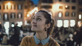 Portrait of young beautiful woman standing in the city centre in evening. Student girl looks at camera, smiling. Brunette female spending weekend in evening Royalty Free Stock Image