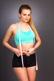 Portrait of young beautiful woman standing with measuring tape Royalty Free Stock Photography