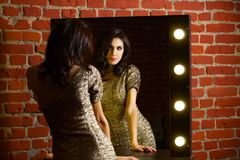 Portrait of young beautiful sexy woman standing near mirror with Royalty Free Stock Photos