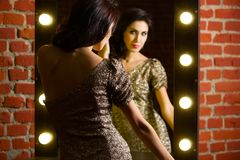 Portrait of young beautiful woman standing near mirror with stock photos