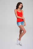 Portrait of young beautiful woman standing on white background. Portrait of young beautiful curly woman in red top, jeans shorts and white sneackers standing on stock photography