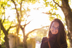 Portrait of a young beautiful woman at sunset in a forest. She i. S smiling. Golden hour. Casual clothing. Lifestyles Royalty Free Stock Photography