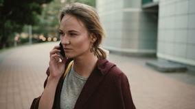 Portrait of young beautiful woman talking with friends, using the smartphone. Female standing outside and speaking. Portrait of young beautiful woman talking stock video