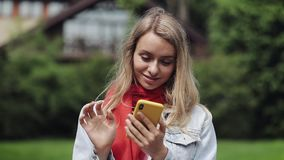 Portrait of young beautiful woman using app on smartphone, smiling and texting on mobile phone. Woman wearing in the red. Scarf standing near a country house stock video