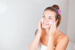 Portrait of young beautiful woman using cosmetics cream Royalty Free Stock Photos