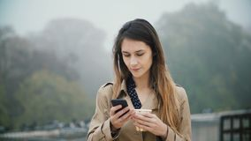 Portrait of young beautiful woman using the smartphone with touchscreen and drinking coffee in early foggy morning. Portrait of young beautiful woman using the stock footage