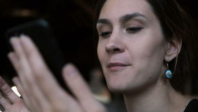 Portrait of young beautiful woman using the smartphone and talking with someone near her. Female typing the message. stock footage