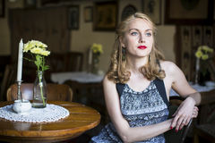 Portrait of young beautiful woman in a vintage cafeteria. Suspense. Royalty Free Stock Images