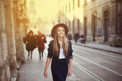 Portrait of young beautiful woman wearing hat walking in the old city. Street fashion concept. Toned Royalty Free Stock Photo