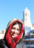 Portrait of a young beautiful woman wearing a hood with ancient buildings backwards during a cold winter morning in Girona Royalty Free Stock Photos