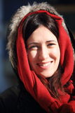 Portrait of a young beautiful woman wearing a hood with ancient buildings backwards during a cold winter morning in Girona Royalty Free Stock Images