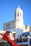 Portrait of a young beautiful woman wearing a hood with ancient buildings backwards during a cold winter morning in Girona Royalty Free Stock Photo