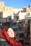 Portrait of a young beautiful woman wearing a hood with ancient buildings backwards during a cold winter morning in Girona Royalty Free Stock Photography