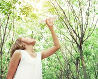 Portrait of young beautiful woman wearing white dress drinking. Water in the green forest royalty free stock photos