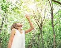 Portrait of young beautiful woman wearing white dress drinking. Water in the green forest royalty free stock photography