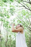 Portrait of young beautiful woman wearing white dress drinking. Water in the green forest royalty free stock images