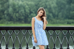Portrait young beautiful woman in white blue striped dress, summer rver park outdoors Royalty Free Stock Photo