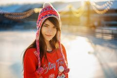 Portrait of a young beautiful woman in winter in a hat in the sun stock photography