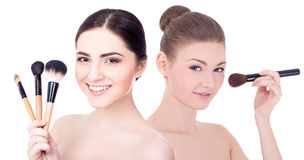 Portrait of young beautiful women applying rouge or powder with Royalty Free Stock Photos